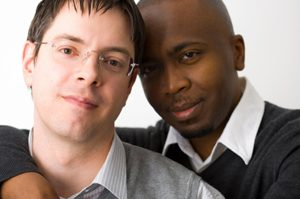 Attractive interracial gay couple, shallow depth of field with focus on man on the foreground.